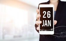 January 26th. Day 26 Of Month, Calendar Date. White Smartphone With Calendar Date In Businesswoman Hand On Blurred Background. Winter Month, Day Of The Year Concept.