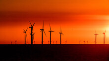 Offshore Wind Turbines Set Against A Sunrise Red Sky