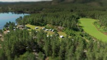 Camping Cozily Tucked In Between The Trees And On The Bank Of The Otra River. Campers, Caravans, Cars, And Tents Scattered On The Grass. Cabins Hidden Under The Tall Pine Trees. A Tilt-shift Video.