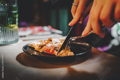 Fototapeta woman hands with knife and fork cutting pizza on table in cafe