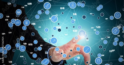 Composition of network of connections with icons over businessman touching interactive screen
