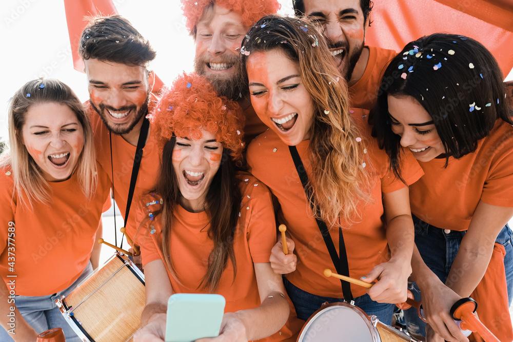 Leinwandbild Motiv - DisobeyArt : Orange sport supporters watching football game on mobile phone - Betting concept - Main focus on center girl face