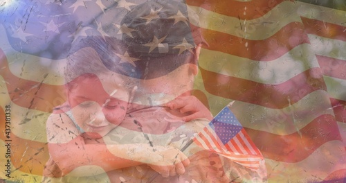 Composition of male soldier embracing smiling daughter over american flag