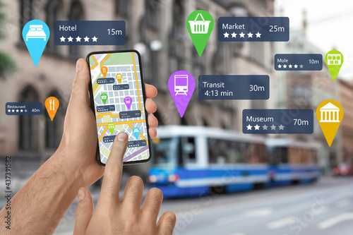 Fotografiet Tourist using online guide application on smartphone for navigation in city, clo