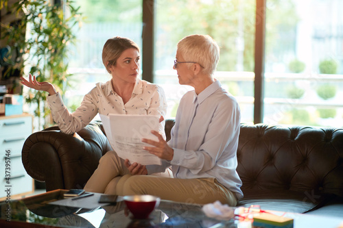 A young business woman and her elderly female colleague discussing some documents they are passing through together while they sitting on the sofa at the office. Business, office, job #437395746