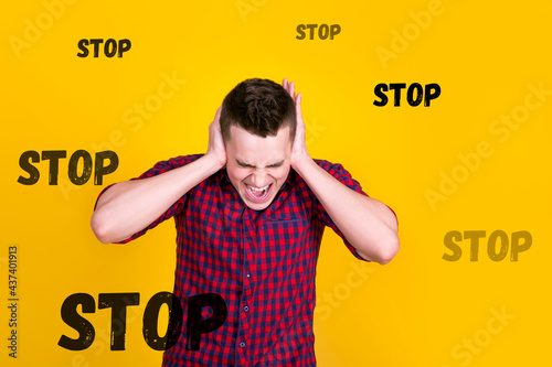 Fototapeta A handsome guy in a red shirt on a yellow background