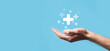 Male hand holding plus icon on blue background. Plus sign virtual means to offer positive thing like benefits, personal development, social network Profit,health insurance, growth concepts
