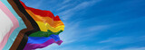 Progress LGBTQ rainbow flag waving in the wind at cloudy sky. Freedom and love concept. Pride month. activism, community and freedom Concept. Copy space. 3d illustration