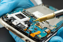 Technician Repairing Inside Of Hard Disk By Soldering Iron. Integrated Circuit. The Concept Of Data, Hardware, Technician And Technology.