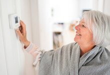 Senior Woman Adjusting Her Thermostat At Home