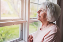 Middle Aged Female In Front Of Curtains Close To A Window Feel Lonely
