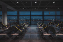 A Wide-angle View Of A Dark Empty Abandoned Quarantined Waiting Hall Of A Modern Airport Terminal At Night, On A Lockdown With Regular Greenish Tapes Over The Seats To Maintain Social Distancing