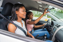 Young Black Teenage Driver Seated In Her New Car With Her Mother
