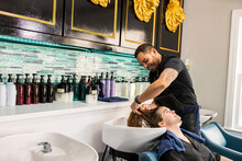 Stylist Washing Young Womans Hair In Sink At Boutique Salon
