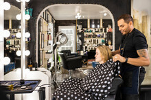 Stylist Sitting Young Woman In Chair After Washing Hair Preparing For Haircut At Boutique Salon