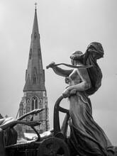Statue In Fountain Across From Steeple