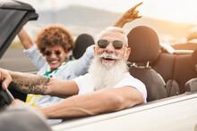 Happy Senior Multiracial Couple Having Fun On Road Trip Summer Vacation Inside Convertible Car