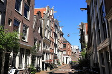 Amsterdam Jordaan Street View With Traditional House Facades And Man On A Bicycle