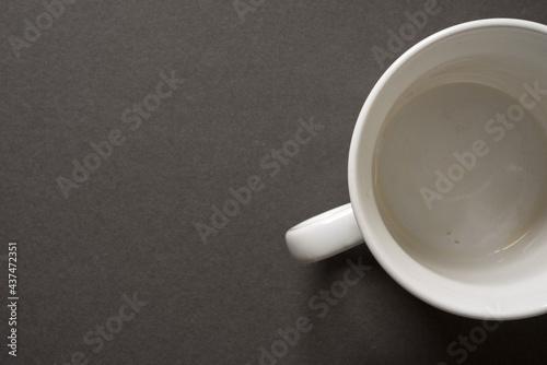 Billede på lærred empty, unwashed white mug or cup on a dark grey background - photographed from a