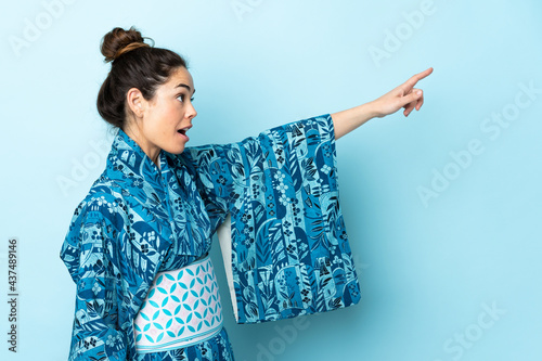 Obraz na plátně Woman wearing kimono over isolated background pointing away