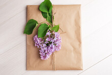 Craft Envelope Decorated With A Purple Lilac Branch On A Light Wooden Table. Top View. Rustic Style. Romantic Concept For Presents.