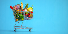 Shopping Cart Full Of Food On Blue Background. Grocery And Food Store Concept.