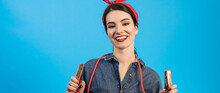 The Happy Woman Holding Jumper Cables On The Blue Background