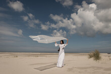 Woman In White Long Dress With Plastic Sheet In The Wind On The Beach