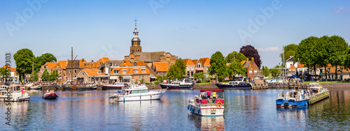 Foto Panorama of historic village Blokzijl in summertime, with boats wating for the l