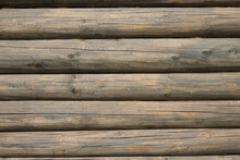 The Wall Of An Old Wooden House Made Of Darkened Weathered Logs. Traditional Russian Log Hut.