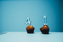 TWO CANDLES STUCK IN TWO CUPCAKES
