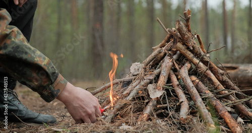 Carta da parati Man starts a fire in the forest using a lighter