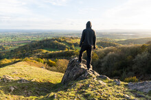 A Hooded Man, Standing On A Rocky Outcrop On Top Of A Hill, Looking Out Across The Countryside In October. Malvern Hills, UK