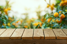 Empty Wooden Table Over Orange Garden Background.  Summer Mock Up For Design And Product Display.