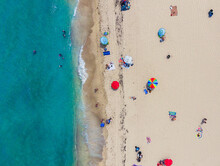 An Aerial Shot Of Tourists Sunbathing On The Sand And Swimming In The Ocean.