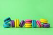 Leinwandbild Motiv Delicious colorful macarons on green background. Space for text