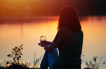 A Young Woman Sits On The Shore Of A Lake, A Glass Of Red Wine In Her Hand, Watching And Enjoying The Sunset
