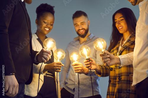 Fotografie, Obraz Group of happy young multiethnic people holding glowing lit retro Edison lightbulbs