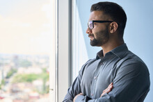 Headshot Portrait Of Indian Confident Successful Businessman In Glasses Thinking Imagining Future Corporate Financial Career Standing At Office Looking At Window. Business Concept.