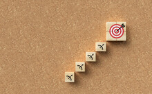 Cubes Forming A Stair Leading To A Target Symbol On Cork Background