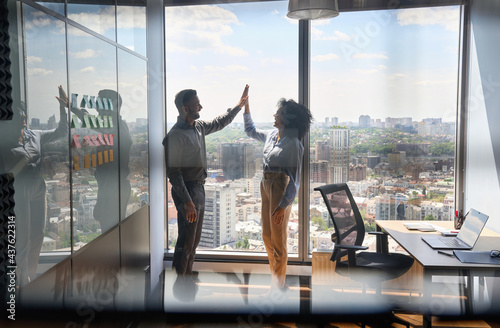 Happy successful indian businessman and African American businesswoman giving high five celebrating business triumph standing in office near urban view panoramic window Fototapeta