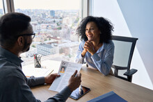 Friendly Interview Between Indian Businessman Hr Director Holding Paper Cv Hiring For Job Female African American Applicant Manager Sitting In Contemporary Office. Human Resources Recruitment Concept.