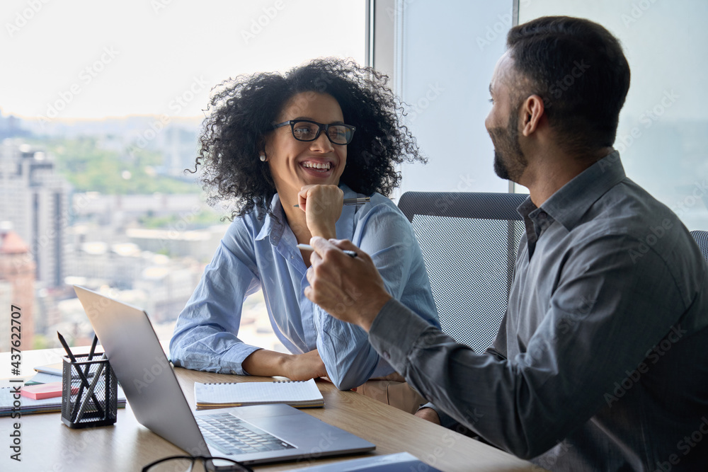 Leinwandbild Motiv - insta_photos : Cheerful happy multiethnic colleagues male indian and mixed race female sitting at desk with laptop working on project together discussing having fun. Corporate business collaboration concept.