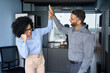 Leinwandbild Motiv Cheerful successful coworkers colleagues indian businessman and African American businesswoman giving high five celebrating project victory in modern office. Business corporate culture concept.