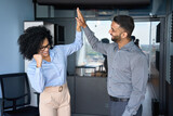 Cheerful successful coworkers colleagues indian businessman and African American businesswoman giving high five celebrating project victory in modern office. Business corporate culture concept.