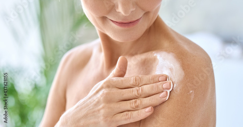 Stampa su Tela Naked middle aged 50s woman pampering herself doing daily routine applying nourishing smoothing body sun cream lotion after shower