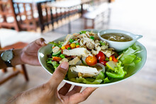 Hand To Served  Salad Of Fresh Tomato,cucumber,onion,spinach, Lettuce And Chicken Fillet In Bowl With Vegetables And Healthy Salad Dressing And Green Lawn Background At The Reataurant With Table.