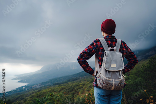 Fototapeta Stylish hipster woman with hat walking on top of mountains.