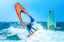 Aquatic Sports: Windsurfers Riding A Wave With An Orange Sail On The Atlantic Ocean