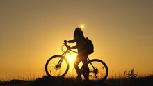 Young Woman Tourist Walks On A Bike, Enjoying The Nature, Fresh Air In Summer Park. A Free Girl Travels On A Bike, Rests, Looks At The Sunset And Enjoys The Sun. Adventure And Travel Concept.